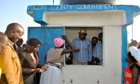 The Governor serving water to residents of Jangoye inside a water-kiosk installed next to the main pumping station of the Jangoye Water System